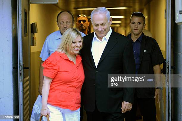 In this handout provided by the GPO Israeli Prime Minister Benjamin Netanyahu and his wife Sara walk out from Hadassah Ein Kerem Hospital after he...
