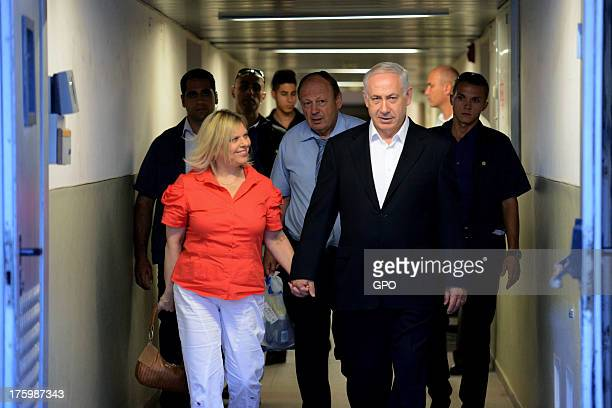 In this handout provided by the GPO, Israeli Prime Minister Benjamin Netanyahu and his wife, Sara walk out from Hadassah Ein Kerem Hospital after he...