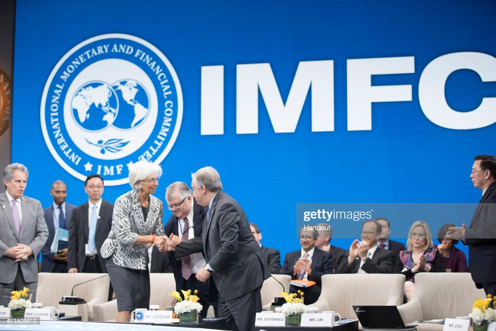 In this handout provided by the IMF, International Monetary Fund Managing Director Christine Lagarde (L) shakes hands with UN General Secretary Antonio Guterres (R) as Chairman Agustin Carstens (C) looks on at the IMFC meeting April 22, 2017 at the IMF Headquarters in Washington, DC. The IMF/World Bank Spring Meetings are being held in Washington this week.