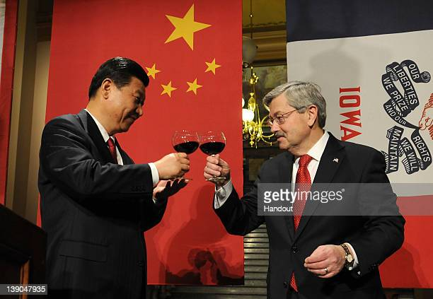 In this handout provided by the Iowa Governor's Office Vice President Xi Jinping of the People's Republic of China and Iowa Gov Terry Branstad raise...