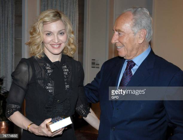 In this handout provided by the Israeli Government Press Office , actress and singer Madonna presents Israeli President Shimon Peres With a Kabbalah...