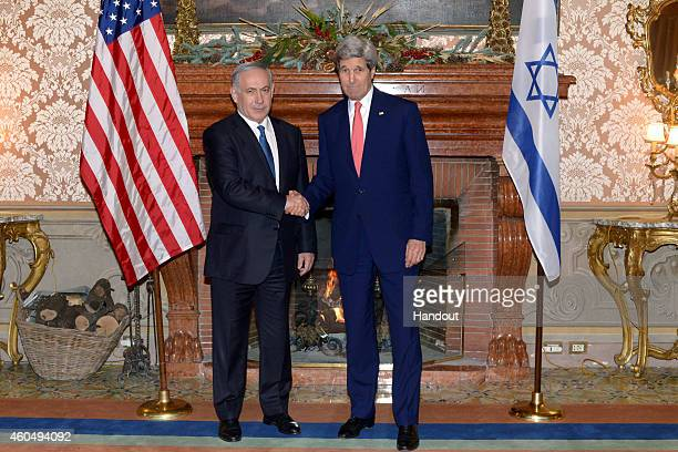 In this handout provided by the Israeli Government Press Office Israel Prime Minister Benjamin Netanyahu shakes hands with US Secretary of State John...