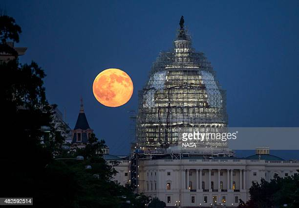 In this handout provided by the National Aeronautics and Space Administration a second full moon for the month of July rises behind the dome of the...