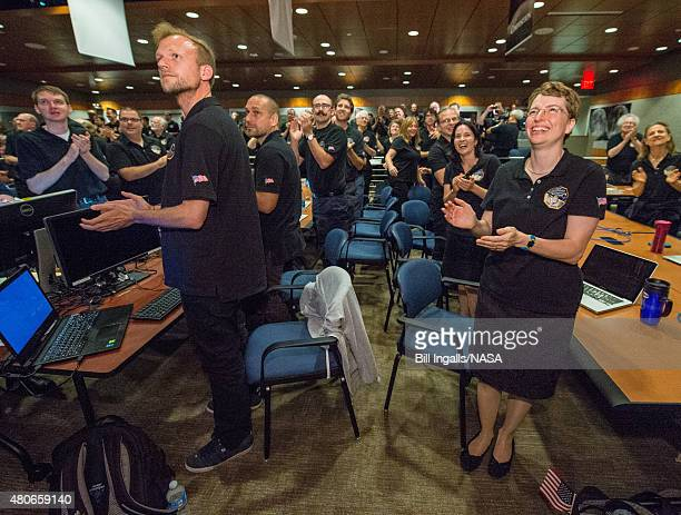 In this handout provided by the National Aeronautics and Space Administration members of the New Horizons science team react to seeing the...