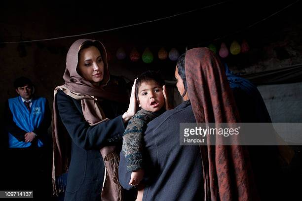 In this handout provided by the UNHCR UNHCR Goodwill Ambassador Angelina Jolie meets with Khanum Gul a mother of 8 and her youngest son Samir at...