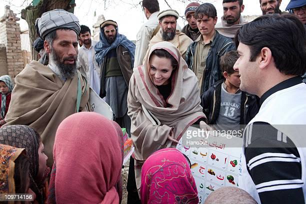 In this handout provided by the UNHCR, UNHCR Goodwill Ambassador, Angelina Jolie presents education materials to both local Headteacher, Gul Rahman,...