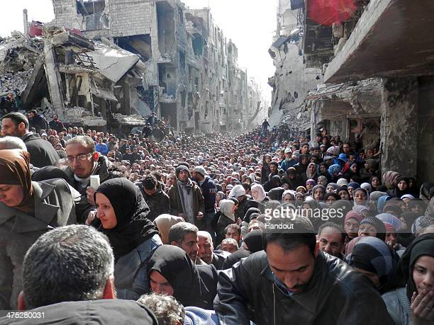 In this handout provided by the United Nation Relief and Works Agency Residents wait in line to receive food aid distributed in the Yarmouk refugee...