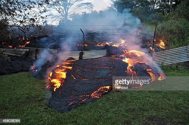 In this handout provided by the US Geological Survey A portion of the front of the June 27th lava flow pushes through a fence marking a property...