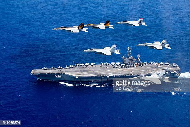 In this handout provided by the US Navy a combined formation of aircraft from Carrier Air Wing 5 and Carrier Air Wing 9 pass in formation above the...