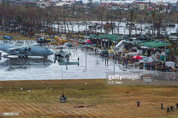 In this handout provided by the US Navy an MH60S Sea Hawk helicopter from the Island Knights of Helicopter Sea Combat Squadron 25 drops supplies onto...