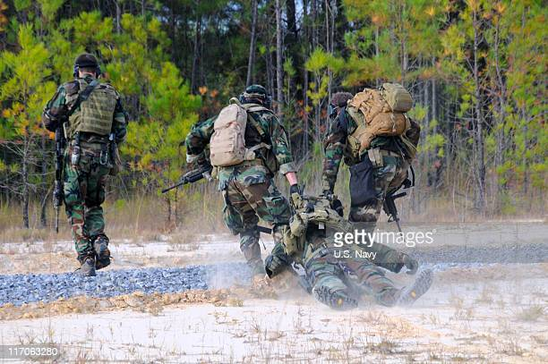 In this handout provided by the U.S. Navy, Navy SEALs simulate the evacuation of an injured teammate during immediate action drills October 25, 2010...