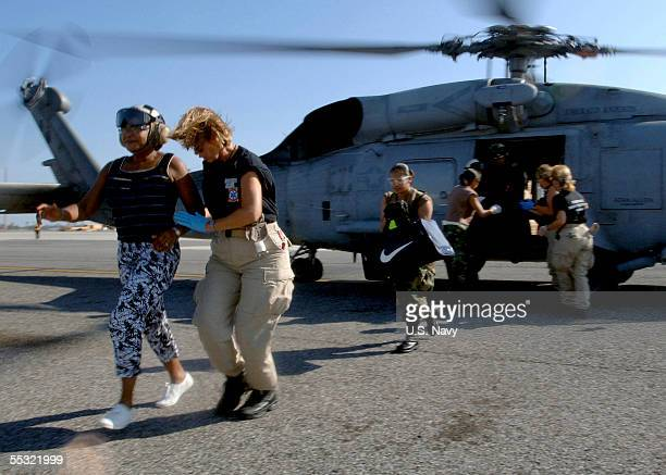 In this handout provided by the US Navy New Orleans residents are rushed from a US Navy Seahawk helicopter after being evacuated from their homes and...
