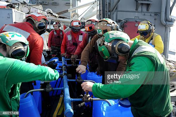 In this handout provided by the US Navy Sailors fill containers with fresh water using a water purification system which will be loaded onto...