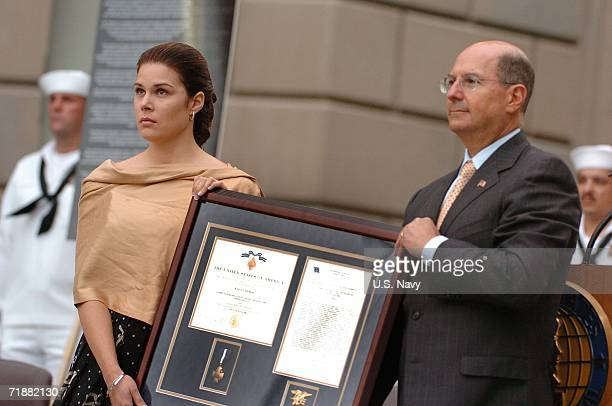 In this handout provided by the US Navy Secretary of the Navy Dr Donald C Winter presents the Navy Cross to Maria Paz Leveque the wife of Gunners...