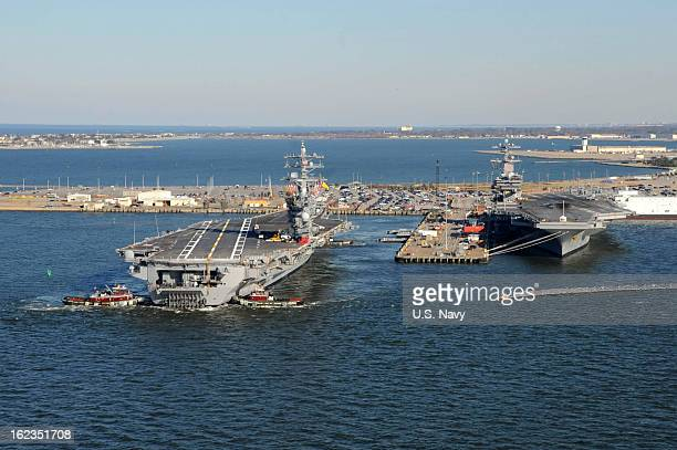 In this handout provided by the US Navy tug boats assist the Nimitzclass aircraft carrier USS Dwight D Eisenhower as it pulls away from the pier...