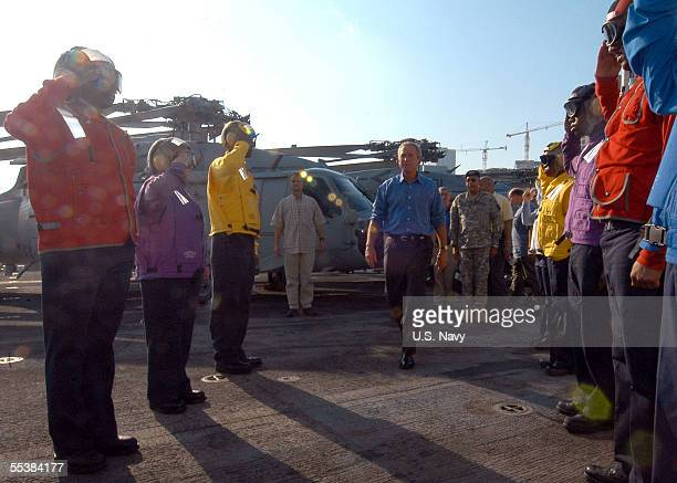 In this handout provided by the US Navy US President George W Bush walks through rainbow sideboys as he arrives aboard the amphibious assault ship...
