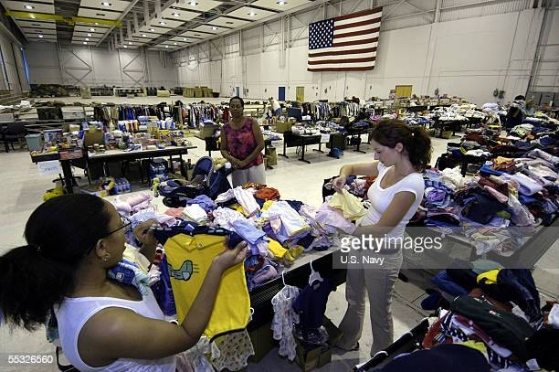 In this handout provided by the U.S. Navy, volunteers sort through baby clothes at the Hurricane Katrina Evacuee Supply Depot, which is housed in a...