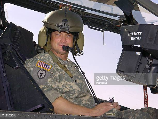In this handout provided by the USO actor Gary Sinise sits in a US Army Apache helicopter during a tour of the flight line May 21 2007 at Contingency...