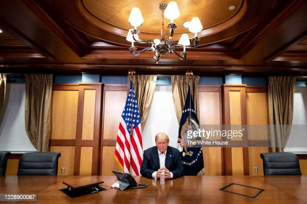 In this handout provided by The White House, President Donald Trump participates in a phone call with Vice President Mike Pence, Secretary of State...