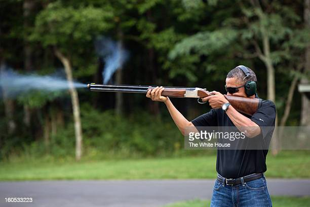 In this handout provided by The White House, U.S. President Barack Obama shoots clay targets with a shotgun on the range on August 4, 2012 at Camp...