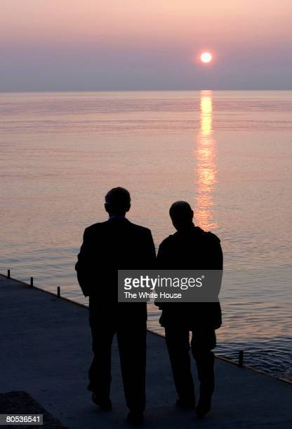 In this handout provided by The White House US President George W Bush and Russia's President Vladimir Putin take a sunset walk on a pier along the...