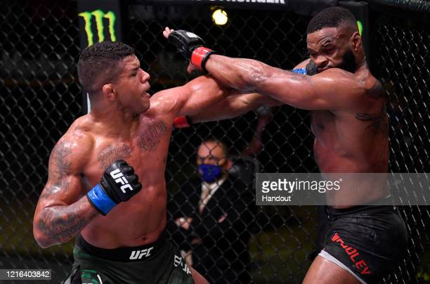 In this handout provided by UFC, Gilbert Burns of Brazil punches Tyron Woodley in their welterweight fight during the UFC Fight Night event at UFC...