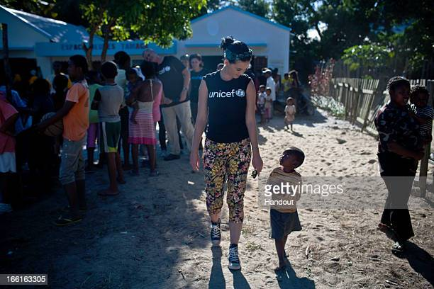 In this handout provided by UNICEF UNICEF supporter Katy Perry walks with a small boy she has just met during her visit to the Tamatave Youth Centre...