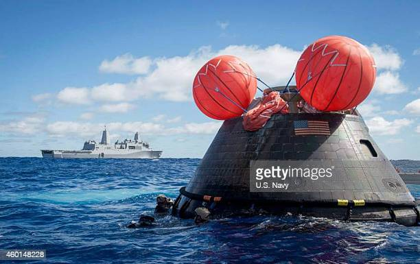 In this handout provided by US Navy Navy divers assigned to Explosive Ordnance Disposal Mobile Unit 11 Mobile Dive and Salvage Company 117 attach a...