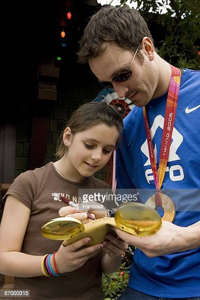 In this handout provided by Walt Disney World 2006 Olympic gold medalwinning snowboarder Seth Wescott autographs a set of golden Mickey Mouse ears...