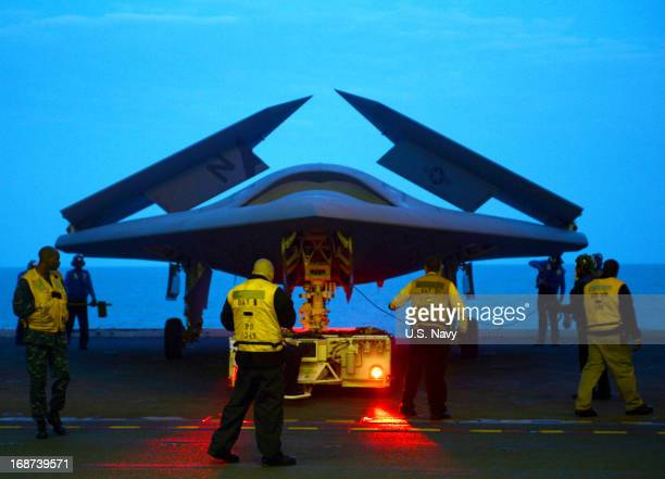 In this handout released by the US Navy an X47B Unmanned Combat Air System demonstrator is towed into the hangar bay of the aircraft carrier USS...