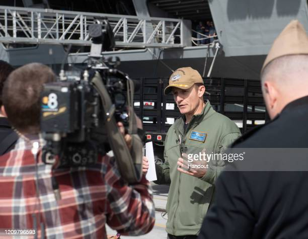 In this handout released by the US Navy Capt Brett Crozier commanding officer of the aircraft carrier USS Theodore Roosevelt addresses local news...