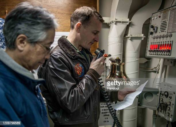 In this handout released by the US Navy Capt Brett Crozier Ronald Reagan's executive officer and Hirokazu Eito a translator conduct a remembrance...