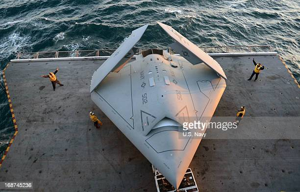 In this handout released by the US Navy Sailors move an X47B Unmanned Combat Air System demonstrator onto an aircraft elevator aboard the aircraft...