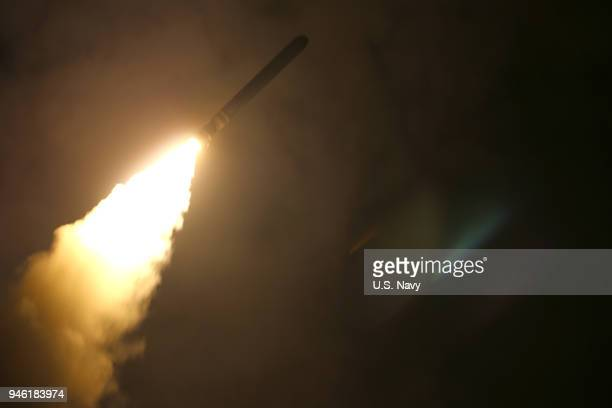 In this handout released by the US Navy the guidedmissile cruiser USS Monterey fires a Tomahawk land attack missile at Syria as part of an allied...