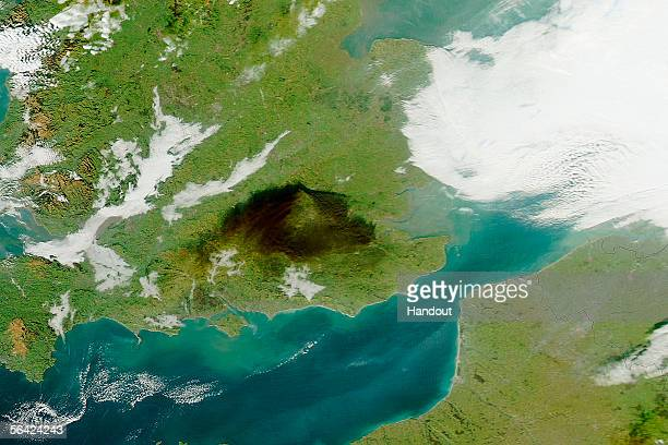 In this handout satellite photo provided by NASA black smoke is seen drifting south from a continuing fire at one of the country's biggest oil depots...