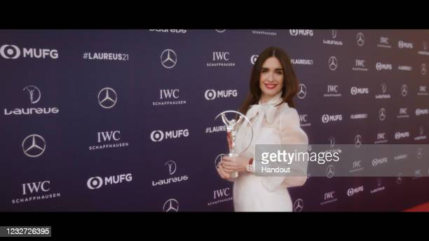In this handout screengrab released on May 6 , Host Paz Vega with a Laureus trophy during the Laureus World Sports Awards 2021 Virtual Award Ceremony...