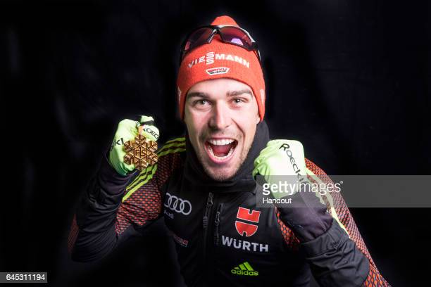 In this handout supplied by NordicFocus Johannes Rydzek of Germany poses with the Gold medal after the medal ceremony for the Men's Nordic Combined...
