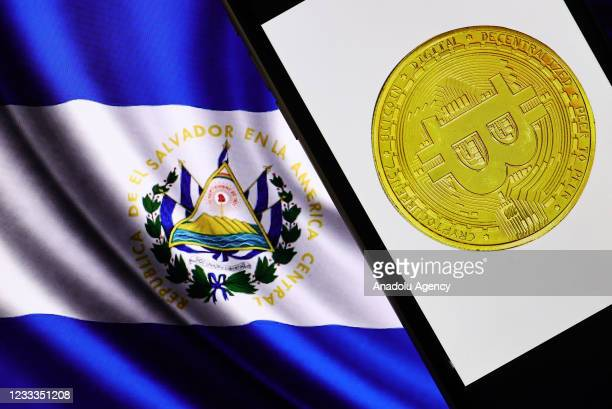 In this illustration photo Bitcoin logo is displayed on a smart phone screen as flag of El Salvador is seen behind, in Ankara, Turkey on June 9, 2021.