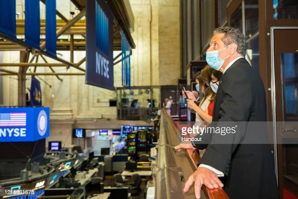 In this image provided by the New York Stock Exchange , Gov. Andrew Cuomo looks over the trading floor at its reopening May 26, 2020 in lower...