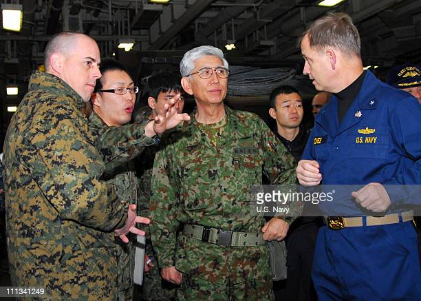 In this image provided by the US Navy Rear Adm Jeffrey S Jones right discusses humanitarian assistance operations with Lt Gen Eiji Kimizuka commander...