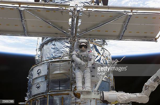 In this image released by the National Aeronautics and Space Administration astronaut Richard M Linnehan works to replace the starboard solar array...