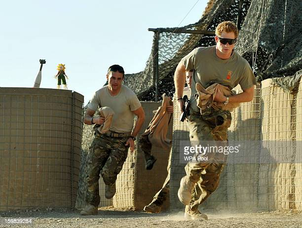 In this image released on January 21 Prince Harry races out from the VHR tent to scramble his Apache with fellow pilots during his 12 hour shift at...