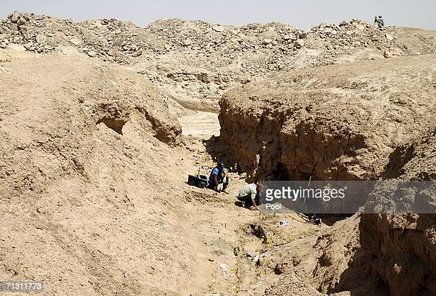 In this image released on June 28 a team of forensic experts work on a mass grave of skeletons in a remote desert south of Baghdad, on June 3, 2006...