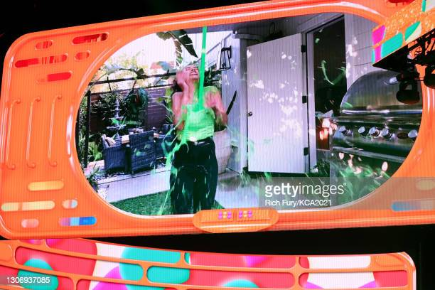 In this image released on March 13, Liza Koshy is slimed on screen during Nickelodeon's Kids' Choice Awards at Barker Hangar on March 13, 2021 in...