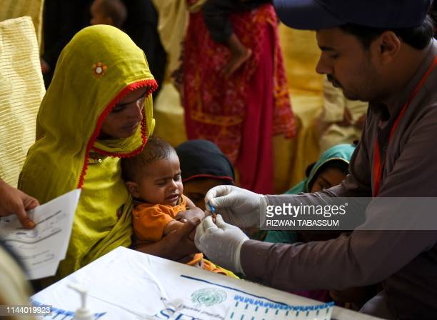 In this image taken on May 9 a Pakistani paramedic takes a blood sample from a baby for a HIV test at a state-run hospital in Rato Dero in the...