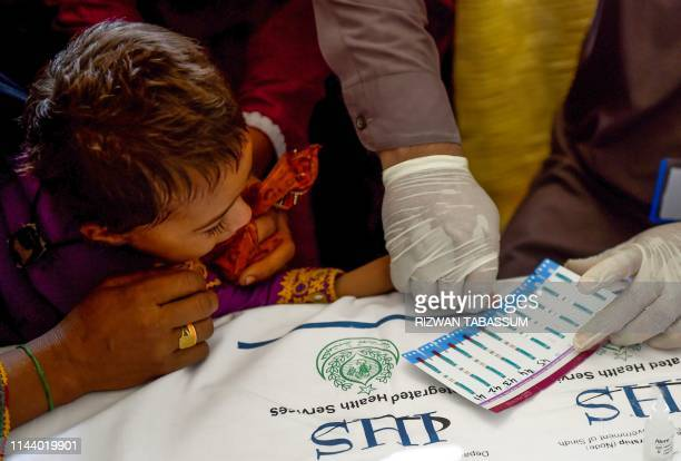 In this image taken on May 9 a Pakistani paramedic takes blood samples from a child for a HIV test at a staterun hospital in Rato Dero in the...