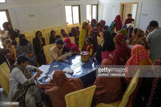 In this image taken on May 9 Pakistani paramedics takes blood samples from children for HIV tests at a staterun hospital in Rato Dero in the district...