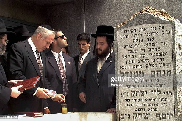 In this Israeli Government Press Office file photo Prime Minister Benjamin Netanyahu lights a memorial candle at the grave of the Lubavitcher Rebbe...