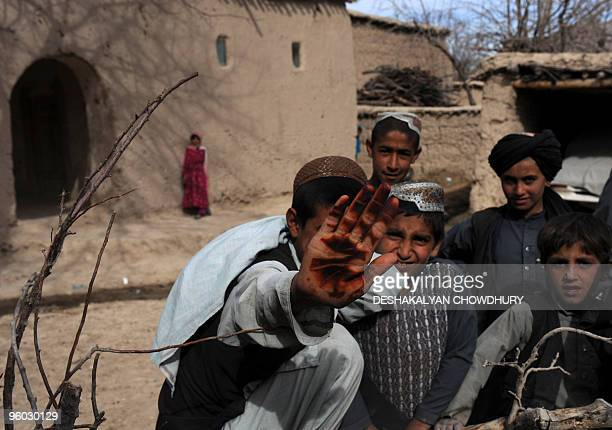 In this January 21 2010 photograph an Afghan girl looks on from a far as a boy shows his hennastained palm to the camera as Dutch soldiers of Charlie...