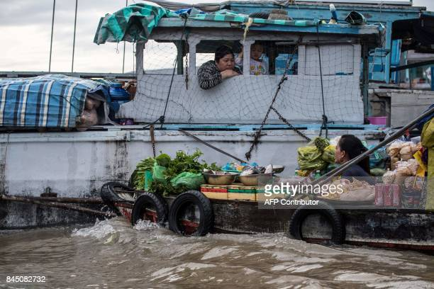 In this July 17 2017 photograph a boat vendor offers her vegetables to a house boat resident in a canal off the Song Hau river in the floating Cai...